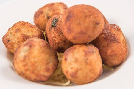 A dish of salt Cod Croquettes balls with straw potatoes