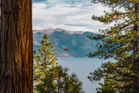 A red helicopter flies over Lake Tahoe near Crystal Bay, Nevada, USA