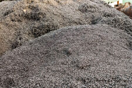 Mountains of aluminium shavings accumulated in a junkyard.