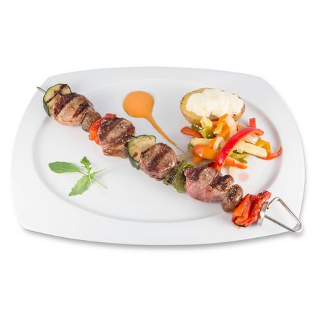 A skewer of iberian pork sirloin with vegetables and baked potato