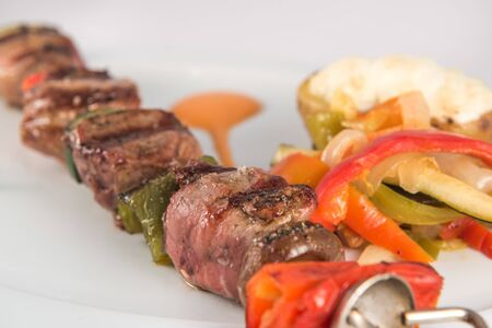 Detail of a skewer of iberian pork sirloin with vegetables and baked potato 版權商用圖片