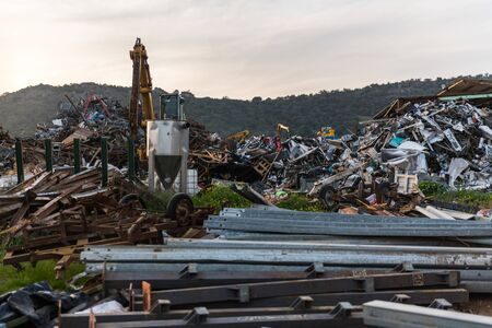 A metal mountains and a crane in a junkyard with some wooded mountains in the background.