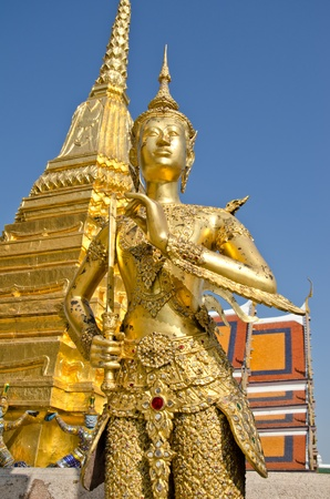 A Golden Kinnari statue at the Temple of the Emerald Buddha (Wat Phra Kaew) , Bangkok, Thailand  photo