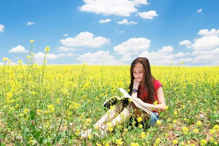 Little girl reads in nature photo