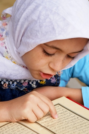 islamic pray: Little girl reads the holy Koran  Stock Photo