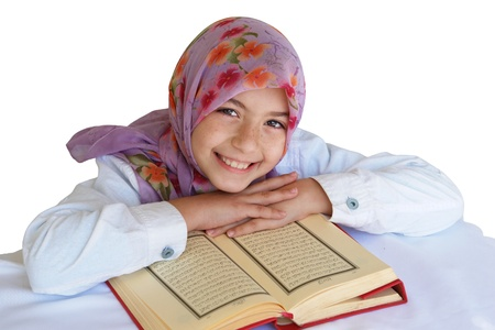 arab hijab: Little muslim girl read her koran and smiles - isolated