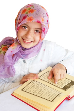 Little muslim girl read her koran and smiles - isolated  photo