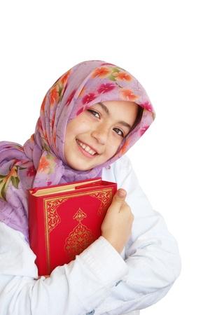 learning pray: Little muslim girl holds Koran