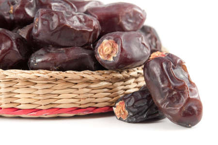 Dates fruits in wicker basket on white background  photo