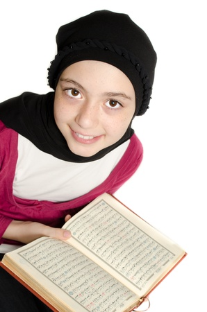 learning pray: Little girl reads Koran (Quran) and smiles  Stock Photo