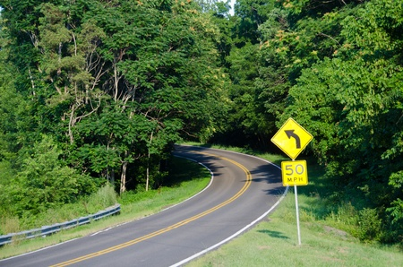 highway signs: Curved forest road in summer