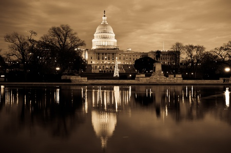 Washington DC, United States Capitol Building and reflection on pond with Christmas tree at sunrise - Sepia Stock Photo