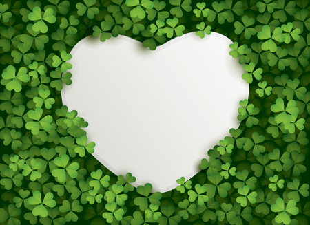 A heart shape blank card surrounded in a patch of clovers.