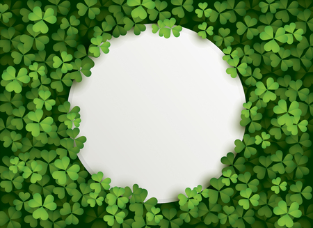 A round shape blank card surrounded in a patch of clovers.
