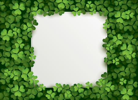 A square blank card surrounded in a patch of clovers.