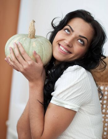 cinderella pumpkin: Attractive girl with dark hair sitting in a wicker chair, holding a green pumpkin and smiling Stock Photo