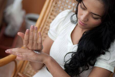 Female applying cream to her hands photo