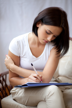 writing pad: Young dark woman writing on notepad to do list at home Stock Photo