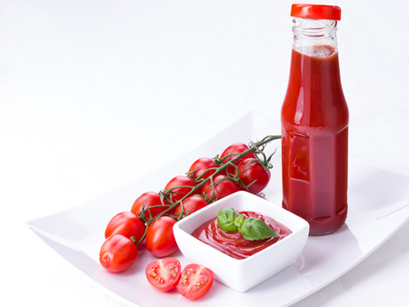 catsup: ketchup, catsup in a glass bottle and a white bowl with cherry panicles tomatoes isolated on white background