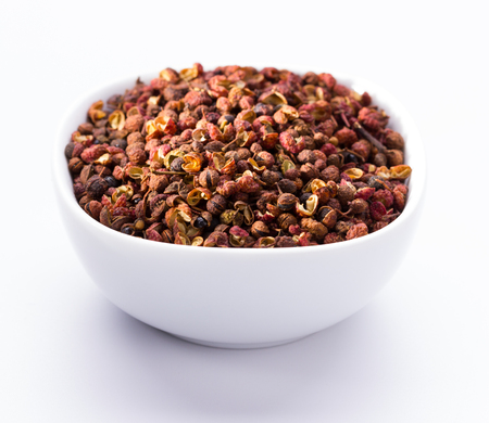 sichuan or japanese pepper in white bowl on white background Stock Photo