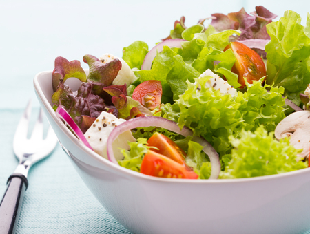 mixed vegetable salad in a white bowl with tomatoes, onions and feta cheese,red leafy lettuce and a fork and napkin