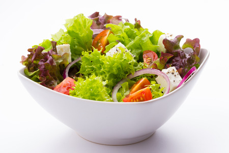 mixed vegetable salad with tomatoes, onions, and feta cheese in a white bowl on white background