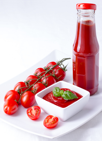 catsup: ketchup, catsup in a glass bottle and a white bowl with cherry panicles tomatoes isolated on white background, verical closeup