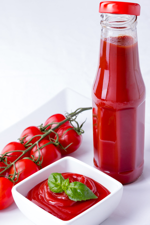 catsup bottle: ketchup, catsup in a glass bottle and a white bowl with cherry panicles tomatoes isolated on white background, vertical closeup Stock Photo