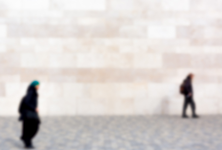 european ethnicity: Man and woman are walking behind one another on walkway, blurred provided with Copy Space