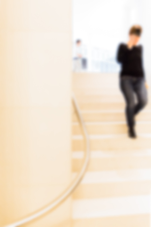 overexposed: Woman in Museum climbing a flight of stairs, man stands up, defocused