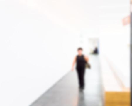 overexposed: Woman walks through a hallway in the museum, defocused, overexposed Stock Photo