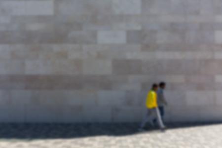 brownstone: Two men in front of stone wall on sidewalk, defocused