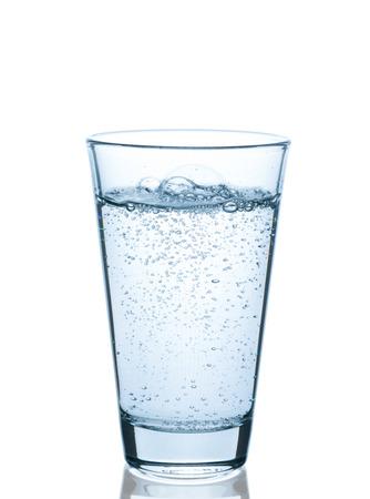 Bicchiere d'acqua che bolle su fondo bianco