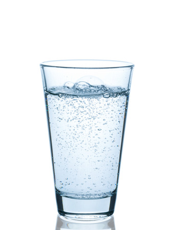 Vaso de agua burbujeante en el fondo blanco Foto de archivo