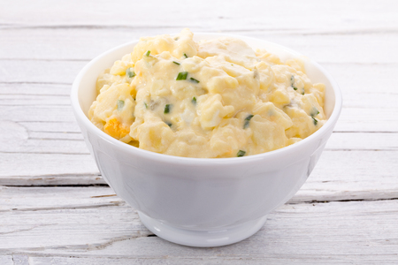 potato salad: potato salad in white bowl on white wooden background
