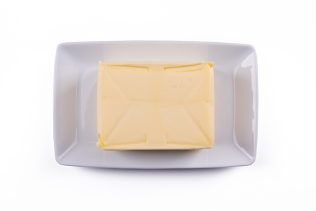 whole block butter on white plate isolated on white background, top view Stok Fotoğraf