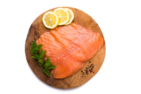 Salmon fillet with lemon, pepper and mint on wooden board, isolated on white background