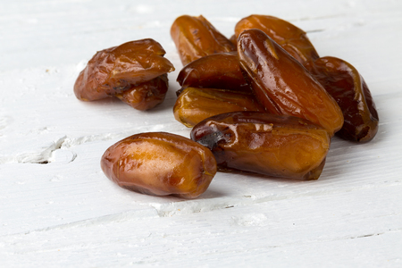 phoenix dactylifera: Group of dates on white wooden background, closeup.