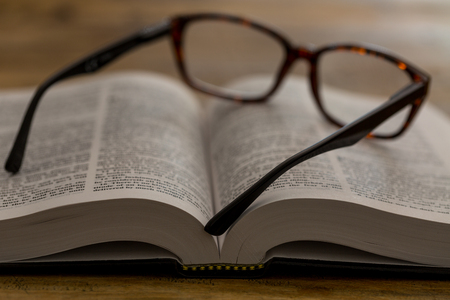 Open book with glasses on brown wooden desk, closeup.