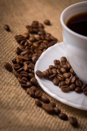 coffeebeans: White cup of coffee with saucer and coffeebeans on linen material, closeup, cutted.