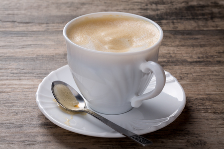 cappuccino foam: Cappuccino with milk foam on wooden background. A spoon with foam is placed on the saucer.