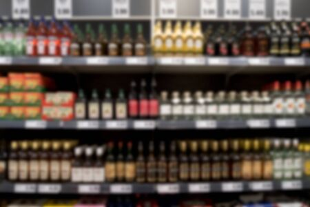spirits: Out of focus supermarket shelf with spirits and wine, unrecognizable Stock Photo