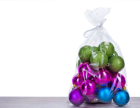 plastic christmas tree: Christmas balls in plastic bag on wooden board and white background Stock Photo
