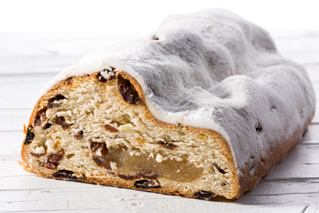 Christmas stollen with raisins and marchpane on white wooden background