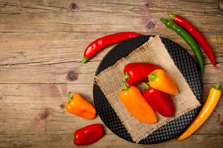 chabby: Red, green ans yellow bell and chili peppers on chabby wooden background, flat lay.