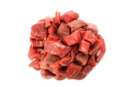 stewing: Heap of raw beef goulash isolated on white background, view from above