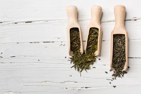 gunpowder: Green tea leaves, bancha, sencha, gunpowder, in scoop on white wooden background with copy-space.