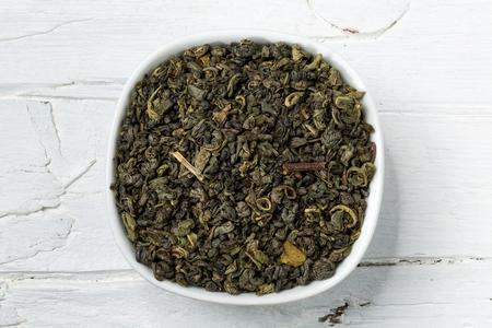 gunpowder: Dried green tea leaves gunpowder in white bowl on white wooden background, view from above.