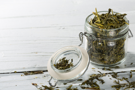 sencha: Dried green japanese sencha tea leaves in jar on white wooden background, closeup with copy-space.