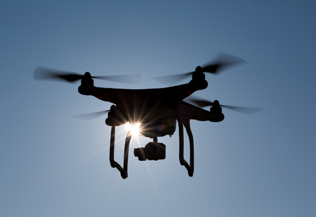 Quadcopter drone flying in front of the sun with backlight, closeup